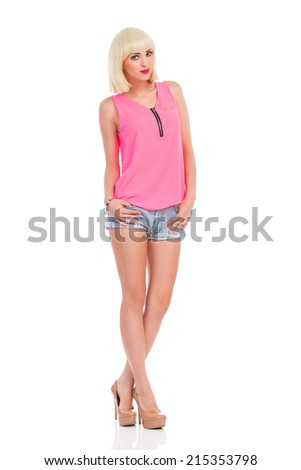 Fashion model posing. Cheerful blond young woman in high heels and pink top posing with hands in pockets. Full length studio shot isolated on white. - stock photo