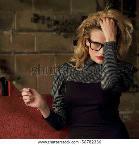 Fashion model posing in an old barn wearing big glasses and smoking a cigarette - stock photo