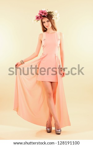 Fashion model posing in pastel clothes on beige background.
