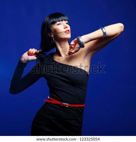 Fashion model posing in studio on a dark blue background - stock photo
