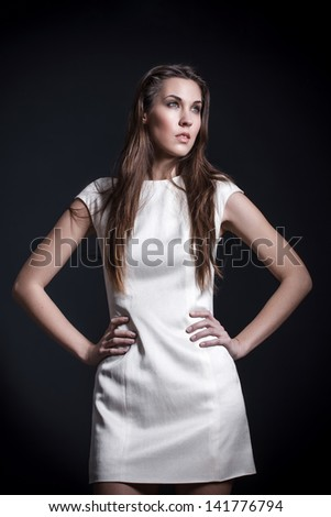 Fashion model posing in white dress, studio - stock photo