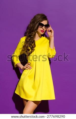 Fashion Model Posing On a Violet Background. Beautiful girl in sunglasses posing in yellow mini dress. Three quarter length studio shot on purple background. - stock photo