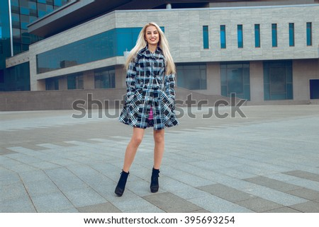 fashion model posing outdoors. fashionable and glamour concept. Young cheerful blonde woman posing outdoors and smiling on the camera - stock photo