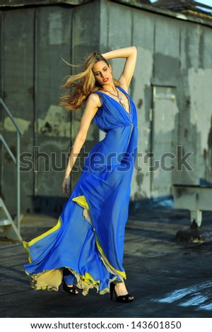 Fashion model posing sexy, wearing long blue evening dress on rooftop location - stock photo