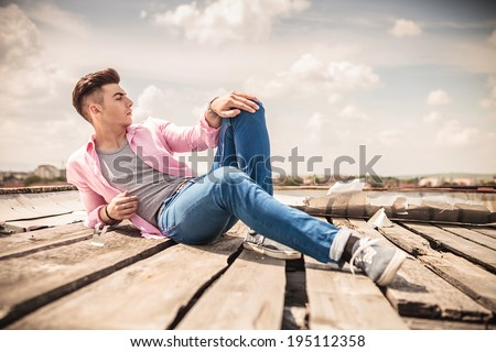 fashion model posing while lying down and looks away - stock photo