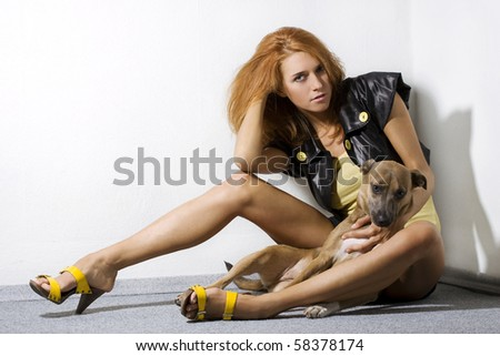 Fashion model posing with dog in the corner of room - stock photo