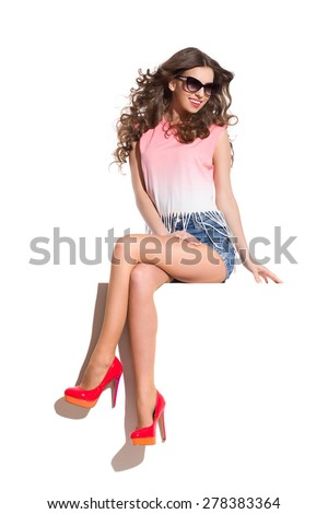 Fashion Model Sitting In the Sunlight. Smiling sexy woman in sunglasses, pink top, jeans shorts and red high heels sitting at the white banner. Full length studio shot isolated on white. - stock photo