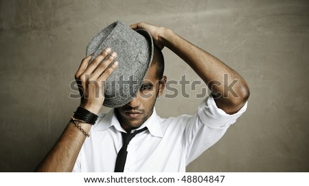 Fashion model tries his best to put his hat on correctly - stock photo