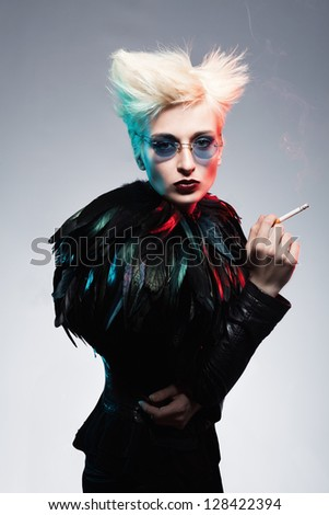 fashion model wearing leather costume with feathers holding a cigarette in her hand on blue background - stock photo