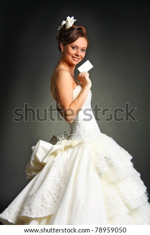 Fashion model wearing wedding dress at black studio background