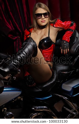 Fashion model wears red clothes sitting on motorbike