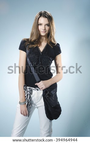 fashion model with bag posing in light background - stock photo