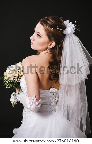 Fashion model with bridal bouquet and glass wearing wedding dress at black studio background.