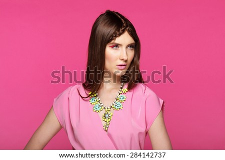 Fashion model with classic make up. Flowers. Spring look. Perfect skin, brunette hair. Pink background.