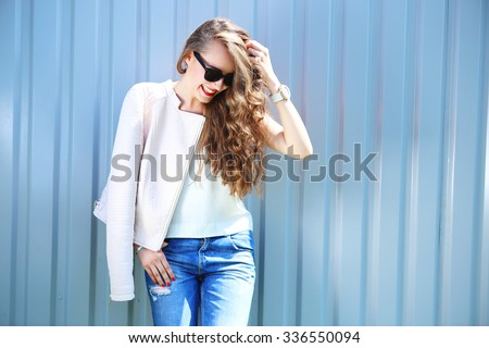 fashion model with long curly hair wearing sunglasses posing outdoor. Jeans, leather jacket. - stock photo