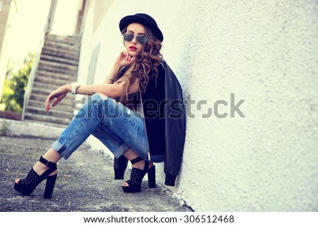 fashion model with long curly hair wearing sunglasses sitting and posing outdoor. Jeans, shoes, hat, jacket. - stock photo