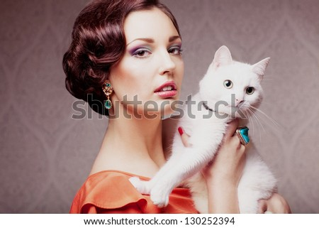 fashion model  with make up hair style and jewelry holding white cat, vintage style - stock photo