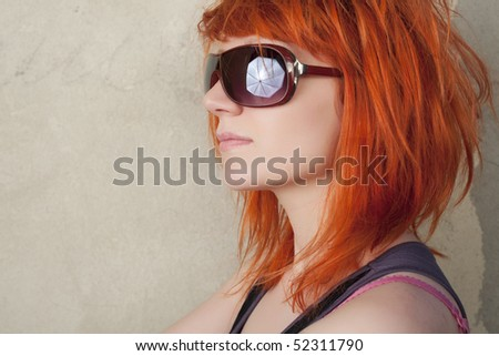 Fashion model with red hair posing on a vintage background
