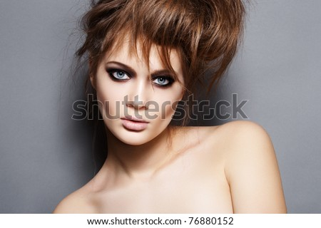 Fashion model with tousled hair, make-up. Portrait of young fashion woman with punk rock hairstyle, dark evening makeup on gray background