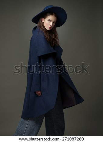 fashion model woman blue coat and hat urban style pose on color background in studio - stock photo