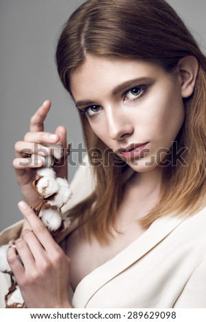 fashion model woman with cotton plant balls in her hands .
