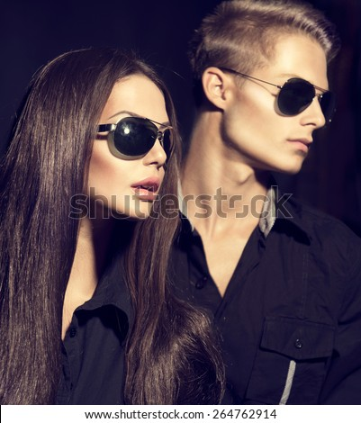 Fashion models couple wearing sunglasses. Sexy woman and handsome young man portrait over dark background. Attractive fashion Boy and girl posing. Hairstyle, haircut
