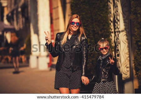 Fashion mom and daughter in leather jackets and gesturing with two fingers - stock photo