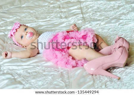 fashion 3 months old baby girl laying on the bed with high heels shoes - stock photo
