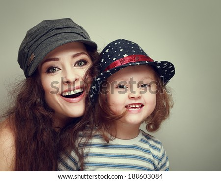 Fashion mother and kid with happy smiling looking in caps. Vintage - stock photo