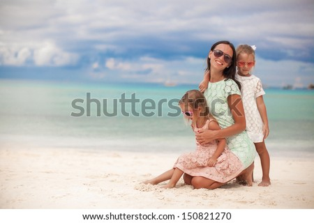 Fashion mother and two her adorable daughters at exotic beach on sunny day - stock photo