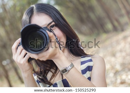 Fashion  of a  autumn girl  wearing a striped  holding the camera - stock photo