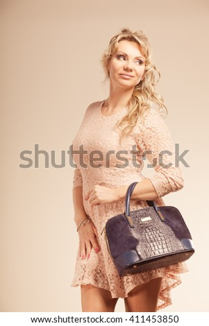 Fashion of women. Clothing and accessories. Mid aged blonde fashionable woman with handbag. Elegant lady on pink.