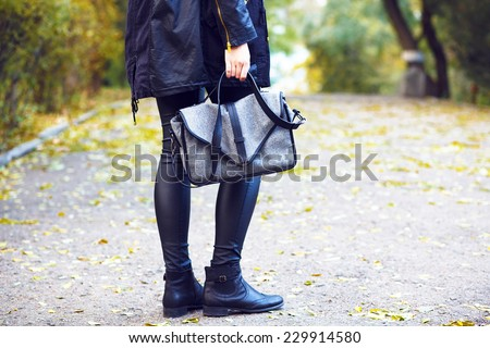 Fashion outdoor image of stylish woman wearing leather pants, warm parka and trendy boots, holding grey bag. Posing at the city park in fall autumn day in the front of yellow leaves. - stock photo