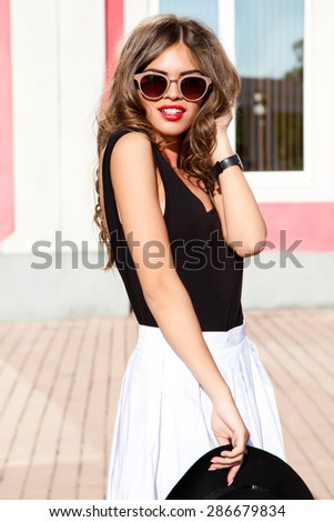 Fashion outdoor  lifestyle portrait of pretty young brunette teenager with bright smoky make up and stylish glasses,trendy outfit,summer skirt,hat,luxury accessories,glamour lady,european fashion - stock photo