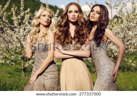 fashion outdoor photo of beautiful charming girls in luxurious sequin dresses posing in blossom spring garden  - stock photo