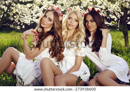 fashion outdoor photo of beautiful charming women in elegant dresses with headband on hair posing in spring blossom garden - stock photo