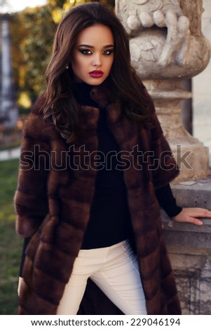 fashion outdoor photo of beautiful elegant woman with dark hair wearing luxurious fur coat,posing in autumn park