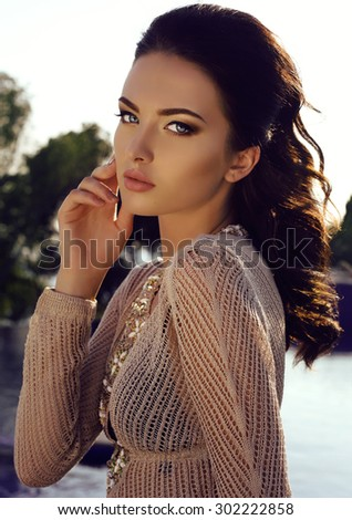 fashion outdoor photo of beautiful girl with dark hair in elegant bikini and transparent beach dress - stock photo