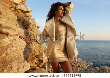fashion outdoor photo of beautiful gorgeous woman with long dark hair wears elegant gold dress and wool coat with accessories,posing on sea coast    - stock photo