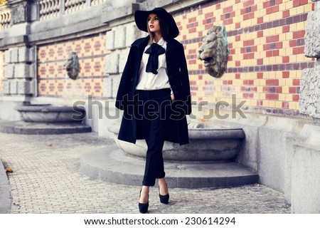 fashion outdoor photo of beautiful ladylike woman with dark hair wearing elegant coat and felt hat and posing in autumn park - stock photo