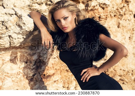fashion outdoor photo of beautiful sensual woman with blond hair wearing elegant black dress and fur,posing on summer beach - stock photo