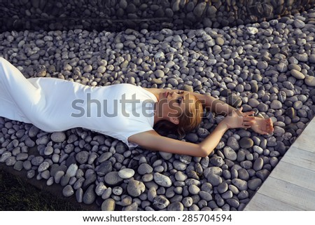fashion outdoor photo of beautiful sexy girl with blond hair in elegant dress posing beside a metallic wall, lying on stones - stock photo