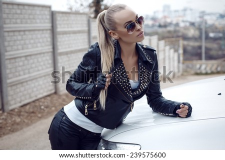 fashion outdoor photo of beautiful sexy girl with long blond hair in leather jacket,posing beside a white car  - stock photo
