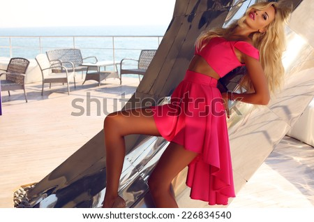 fashion outdoor photo of beautiful sexy woman with blond hair wearing elegant pink dress,posing beside a metallic wall - stock photo