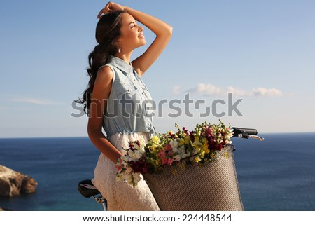 fashion outdoor photo of beautiful smiling girl with dark hair riding bicycle along the sea coast - stock photo