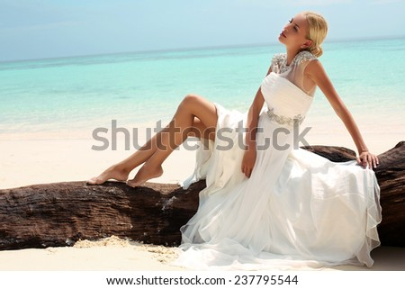 fashion outdoor photo of beautiful woman with blond hair in elegant wedding dress posing on beach in Thailand  - stock photo