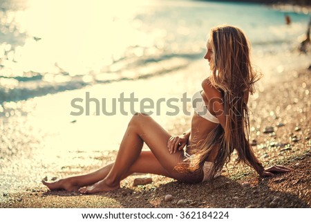 fashion outdoor photo of beautiful woman with blond hair in sexy bikini relaxing on summer beach - stock photo