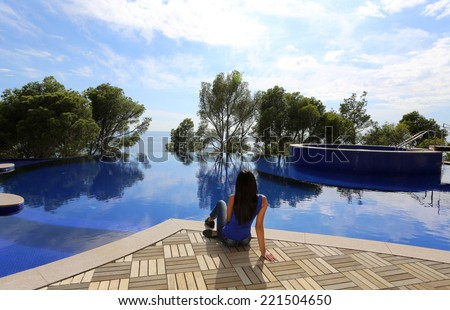 fashion outdoor photo of beautiful woman with dark hair relaxing beside a grand swimming pool - stock photo