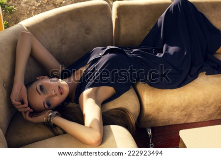 fashion outdoor photo of beautiful young brunette in elegant dress lying on leather divan