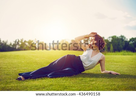 Fashion outdoor photo of beautiful young woman posing on trimmed green grass field. Beautiful tender woman with red hair in dress posing in summer park. - stock photo